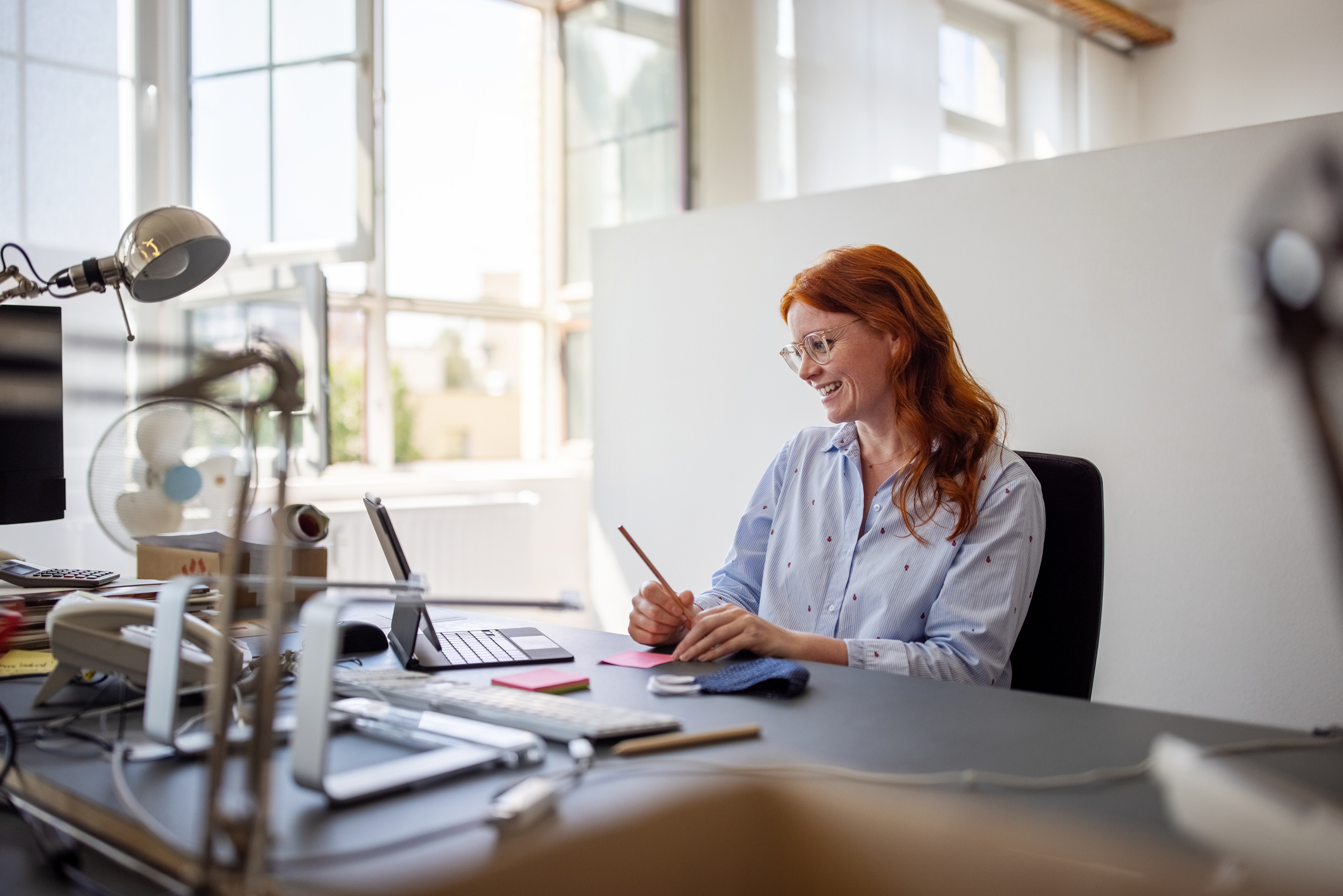 Businesswoman having teleconference from her office desk